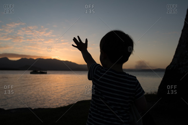 Silhouette of child waving to a boat at sunset