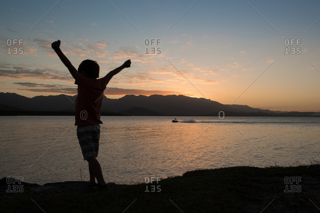 Silhouette of child with arms in the air by mountain sunset