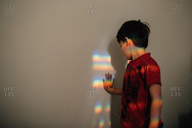 Boy touching colorful light refraction on wall