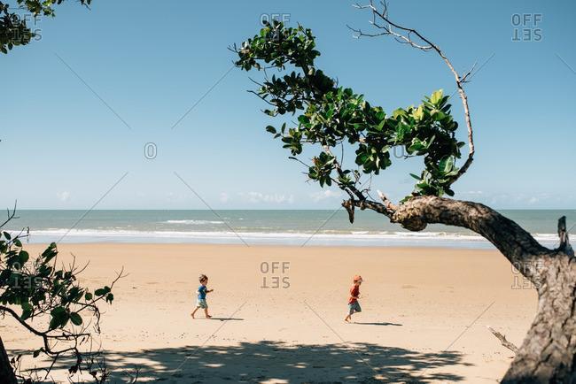 Two little boys running on a beach