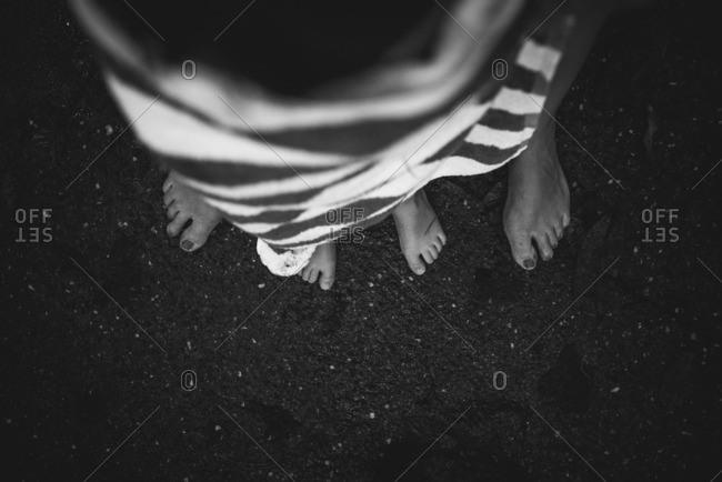 Little boy's feet standing between his mother's feet