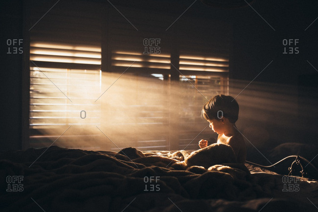 Child sitting on bed with sunlight shining through blinds