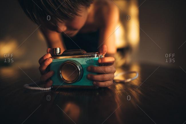 Boy looking at blue camera