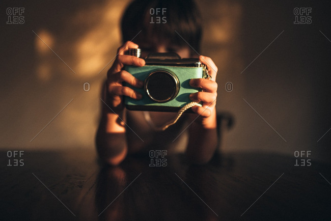 Boy pretending to take picture with blue camera