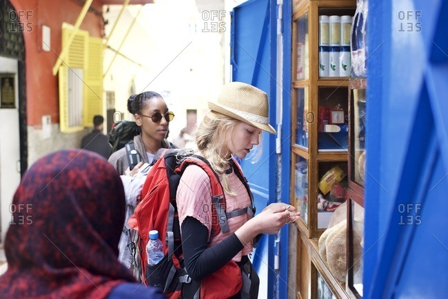 Two young women backpackers shopping in market