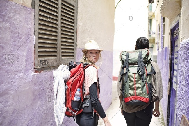 Backpackers walking through alley