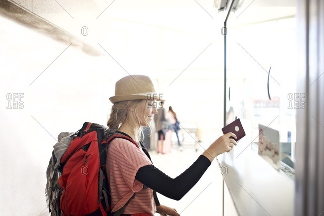 Young woman handing passport to customs agent