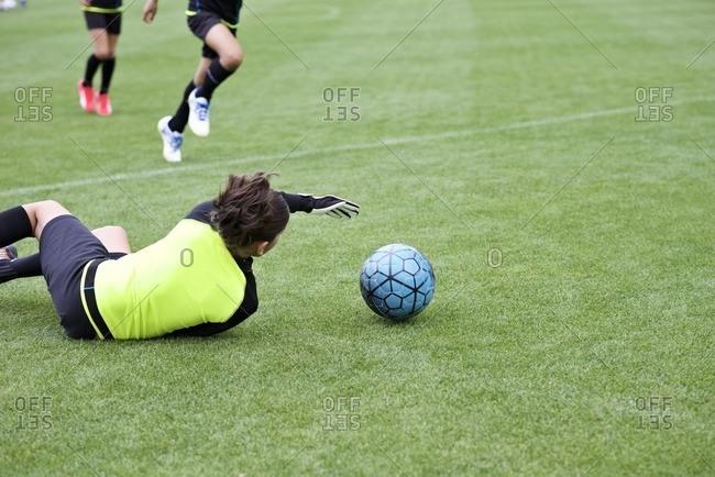 Soccer goalie dives for the ball