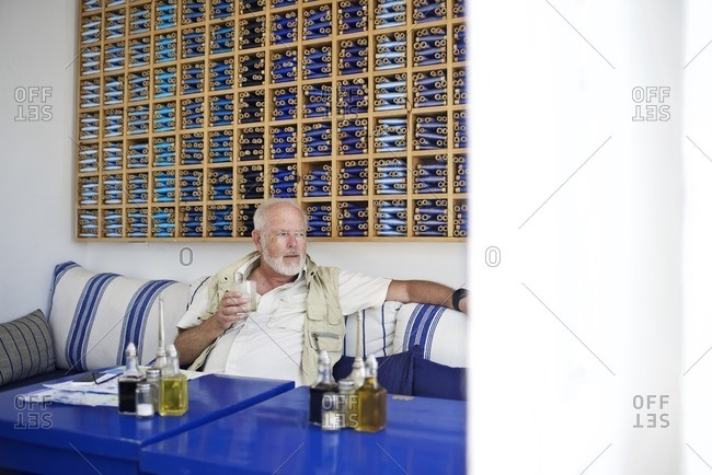 Senior man enjoying drink at cafe