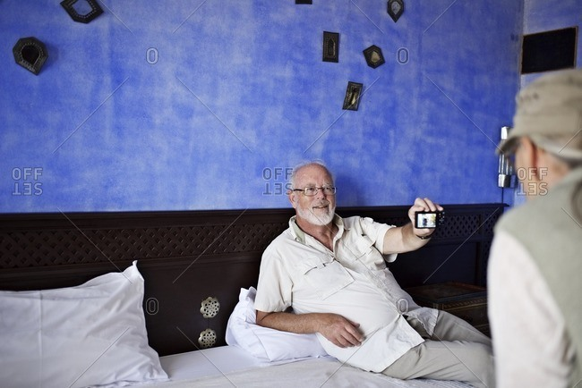 Senior man shows wife photo on digital camera