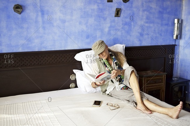 Woman reading book on hotel room bed