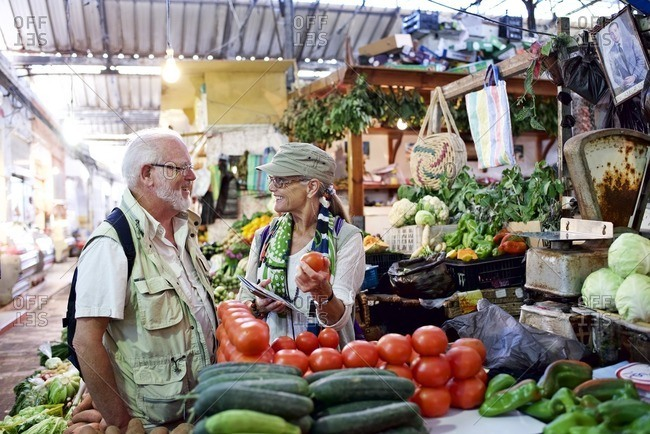 Senior man and woman shop for produce in outdoor market