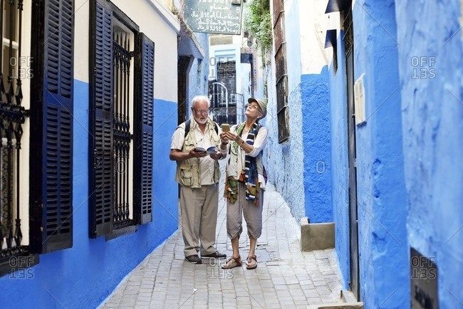 Sightseeing senior couple exploring blue alley