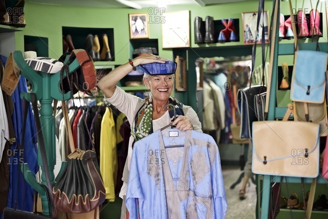 Senior woman trying on hat in boutique