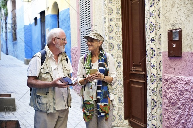 Senior couple exploring streets with smartphone and guide book