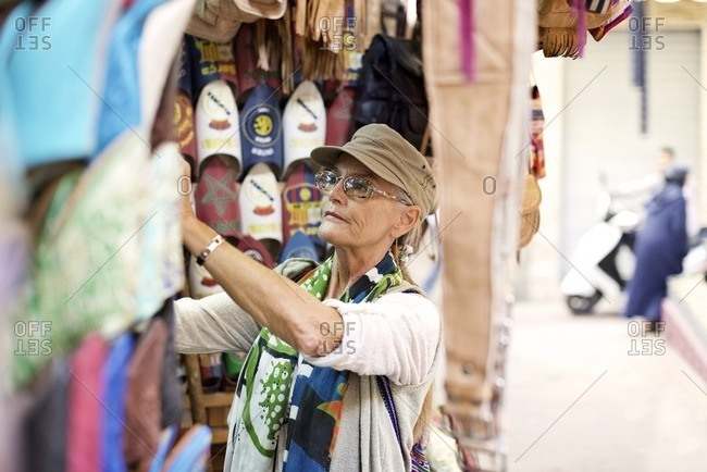 Senior woman looking at slippers in market stall