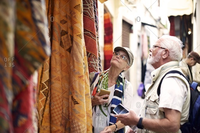 Senior couple shopping for rugs in outdoor market