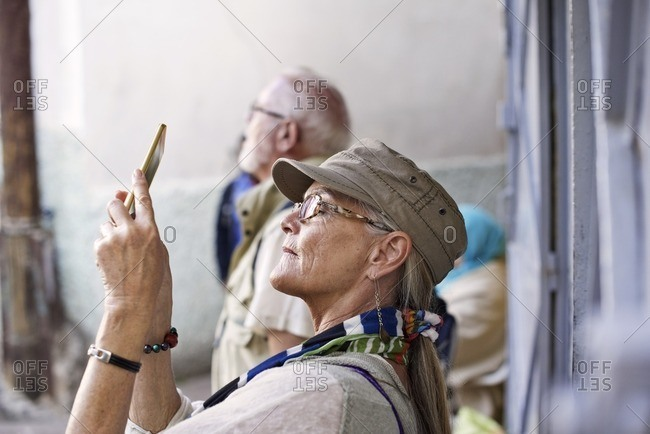 Senior woman takes a picture with her smartphone