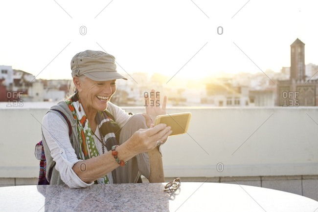 Woman using smartphone on terrace at sunset