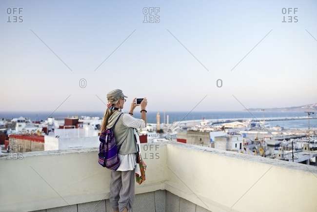 Woman taking a photo of cityscape from terrace