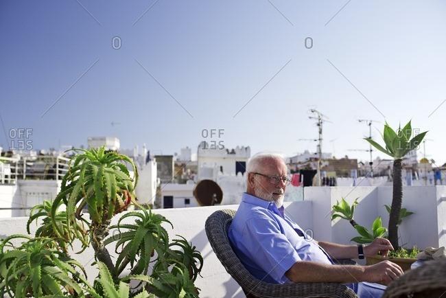 Senior man sitting among plants on terrace