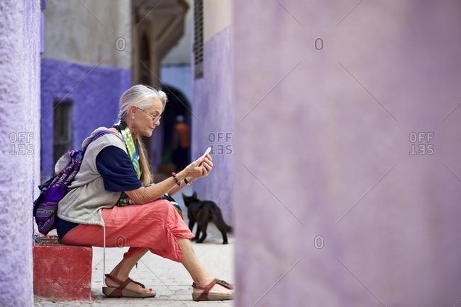 Senior woman sitting on step in purple alleyway