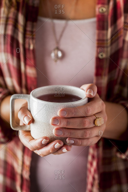 Woman wearing plaid shirt holding a cup of tea