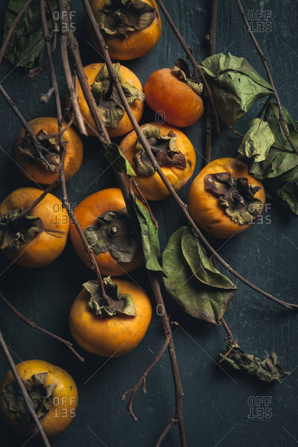 Many fresh persimmons with twigs and leaves
