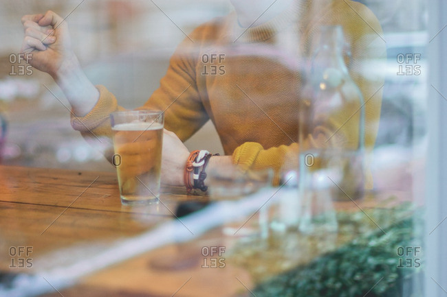 Person in a yellow sweater with bracelets having a drink at a bar