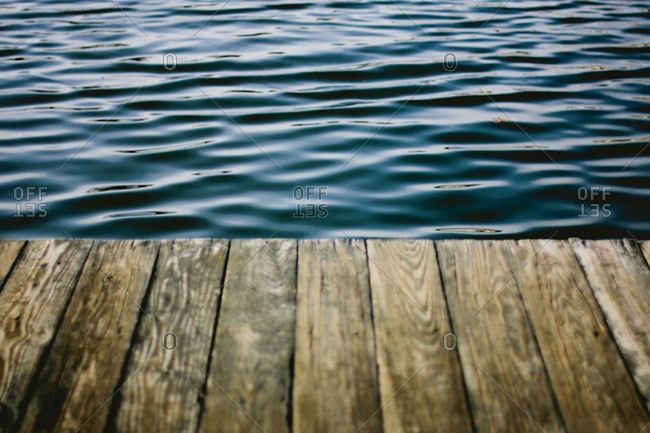 Rippling water at the edge of a wooden dock