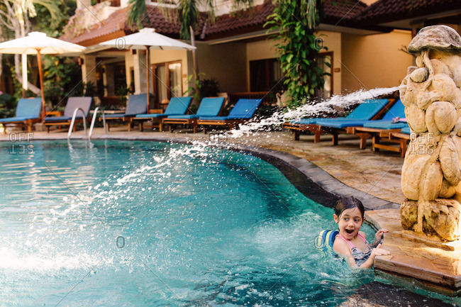 Little girl hanging on to the side of a resort swimming pool