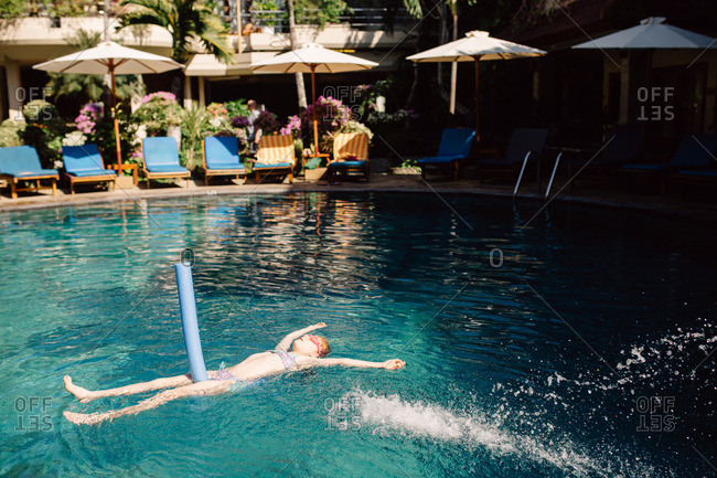 Girl floating on a foam noodle at a resort swimming pool