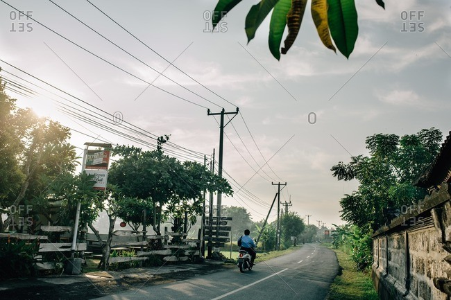 Canguu, Bali, Indonesia - August 30, 2016: Bali, Indonesia - August 30, 2016: Man on a motorized scooter driving past a pizza restaurant