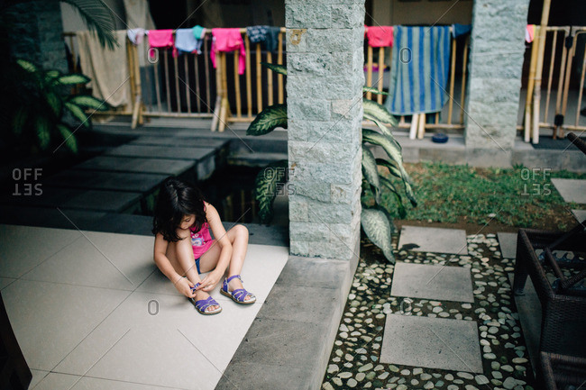 Girl sitting on a patio putting on her shoes