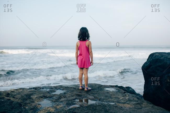 Little girl standing on a rock overlooking a beach