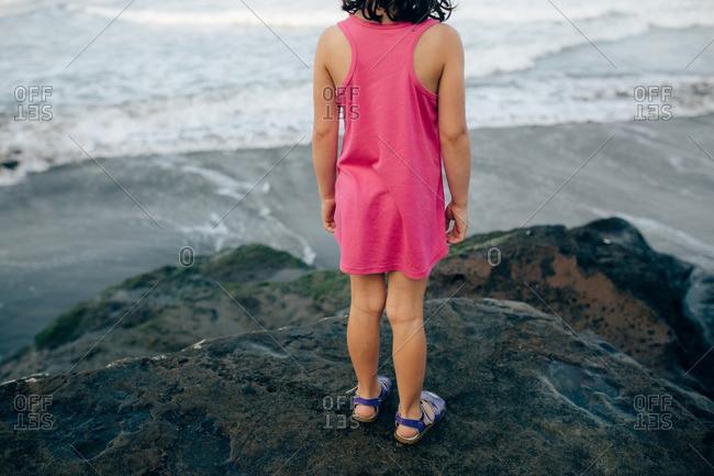 Girl standing on a boulder overlooking a beach