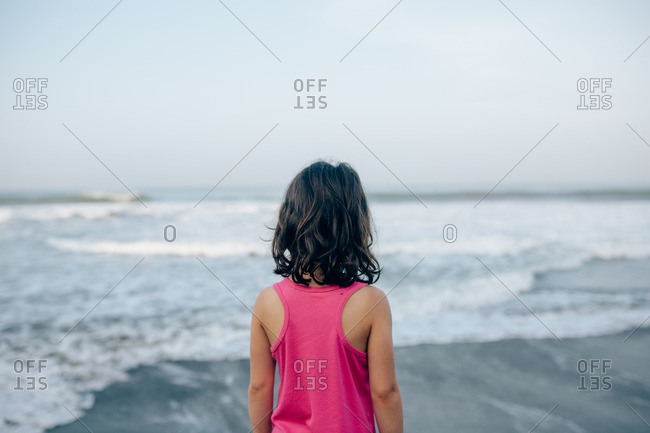 Girl in a pink dress standing on a beach watching the waves