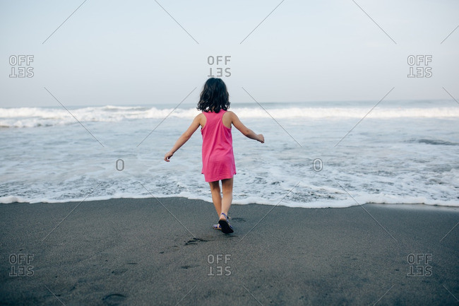 Little girl standing at the edge of the surf on a beach