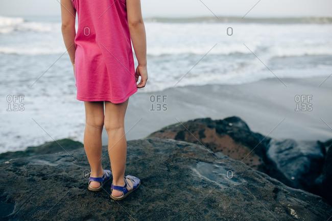 Legs of a girl standing on a boulder overlooking a beach