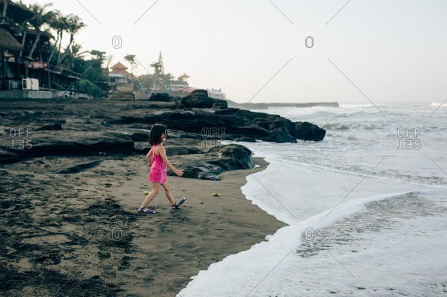 Girl playing on a beach at sunset