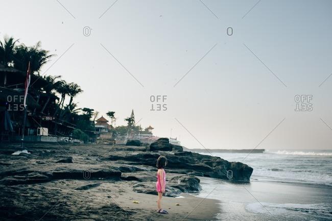 Little girl standing on a beach at sunset