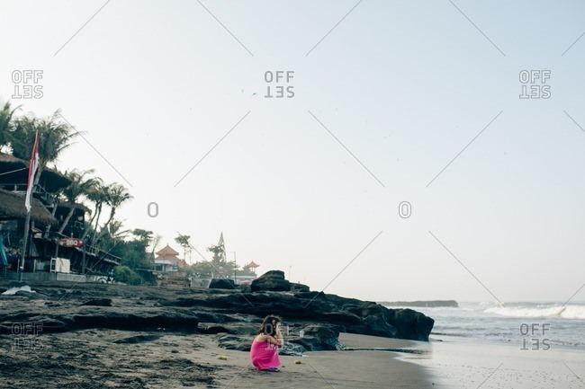 Girl crouching on a beach looking at the waves