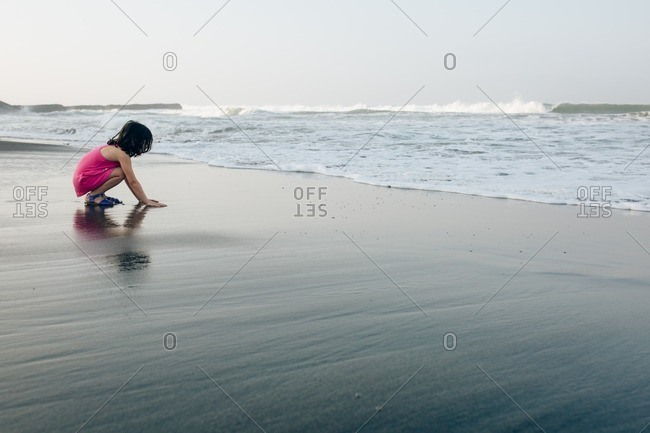 Little girl touching wet sand on a beach at sunset