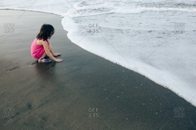 Girl playing at the edge of the ocean at sunset