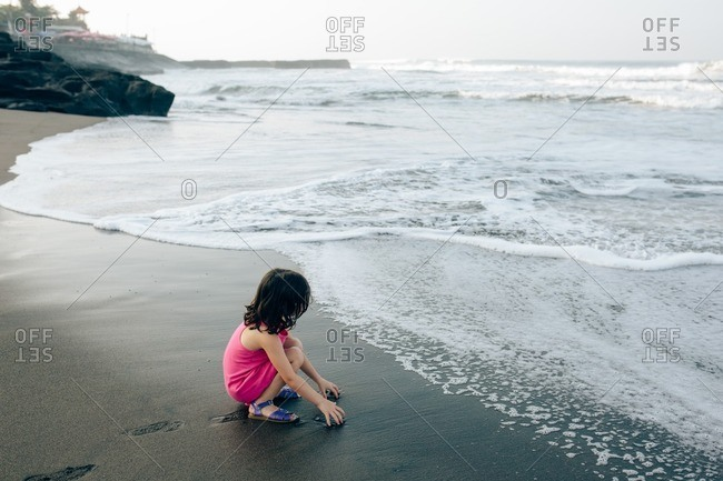 Girl playing in wet sand on a beach at sunset
