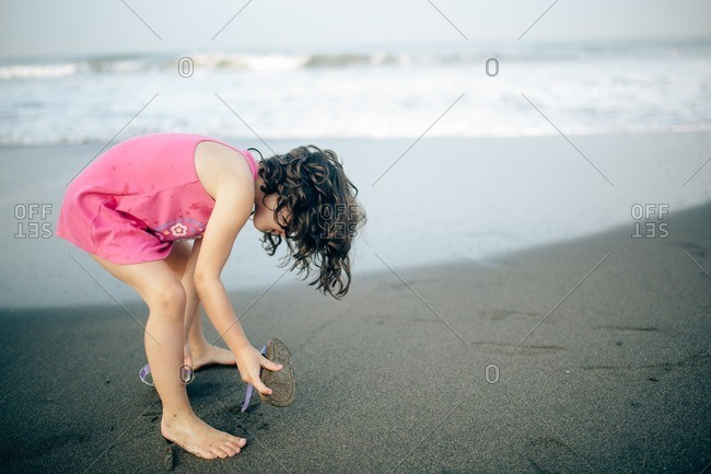 Girl taking off her shoes on a beach at sunset