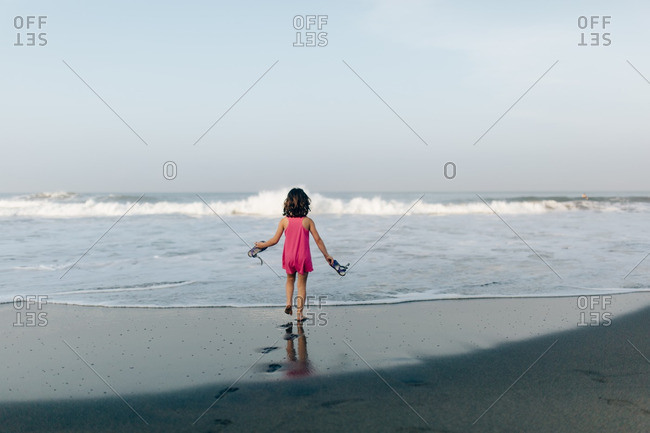 Girl holding her shoes at the edge of the ocean at sunset