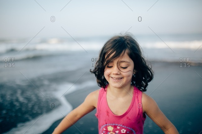 Girl standing on a beach smiling