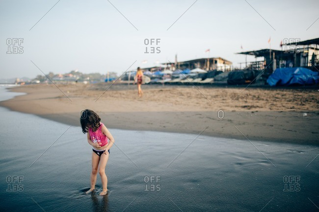 Girl playing on a beach in front of empty shops