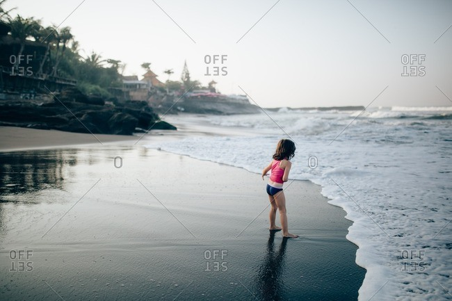 Little girl playing in surf on a beach at sunset